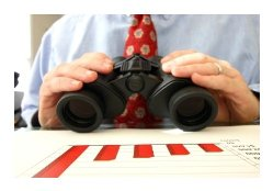 Man holding binoculars in front of a graph.