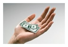 Photo of a hand holding very small dollar bills.